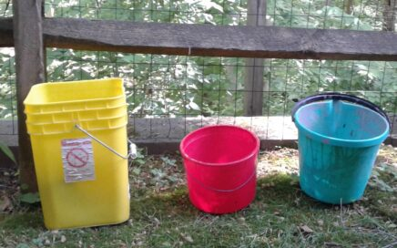 Image of three colored buckets sitting in front of a split rail fence