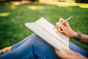 Image of person writing in book by StockSnap from Pixabay
